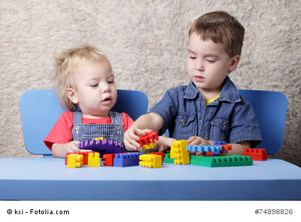 Two cute boy playing lego table